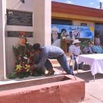 Hijo de la pareja de activistas asesinados pone flores en el  memorial de Ismael y Manuelita frente al edifcio del comisariado ejidal en ejido Benito Juárez. Fotografía de Bryan Soto.